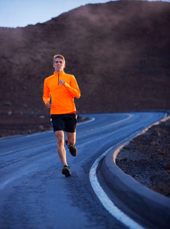 Athletic man running outside, training outdoors. Jogging on road  photo