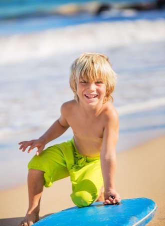 Muchacho joven feliz que se divierte en la playa de vacaciones, con tabla de surf Foto de archivo - 23580560