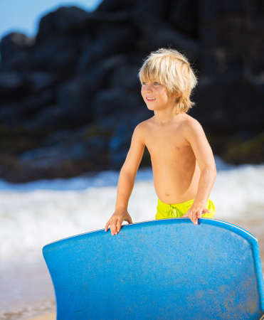 boy swim: Happy Young boy having fun at the beach on vacation, with boogie board