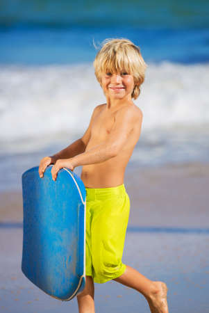Happy Young boy having fun at the beach on vacation, with boogie board photo