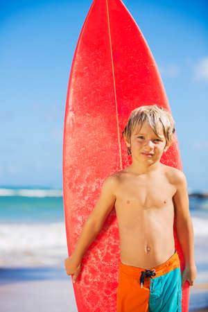 Young surfer, happy young boy at the beach with surfboard photo