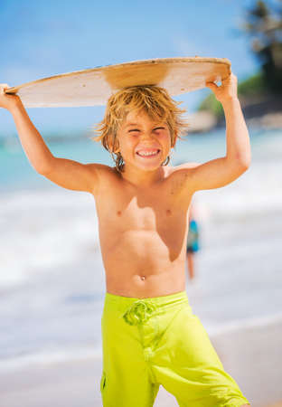 Happy Young boy having fun at the beach on vacation, with skimboard photo
