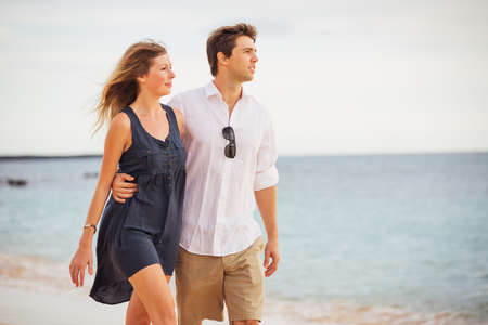 Romantic happy couple walking on beach at sunset. Smiling with arms around each other. Man and woman in love Banco de Imagens