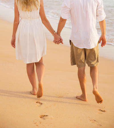Romantic couple holding hands walking on beach at sunset. Man and woman in love. Footprints in the sand.  Banco de Imagens