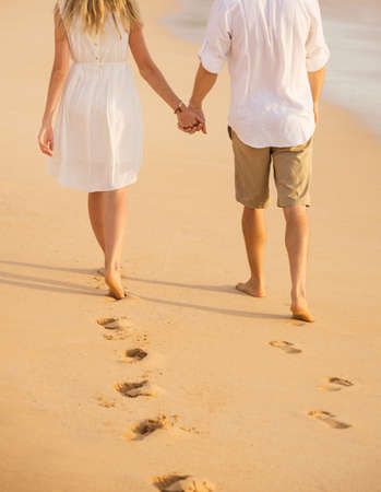 Romantic couple holding hands walking on beach at sunset. Man and woman in love. Footprints in the sand.  版權商用圖片