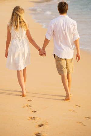 로맨틱 커플 일몰 해변에 산책하는 손을 잡고. 남자와 사랑에 여자. 모래에 발자국입니다.