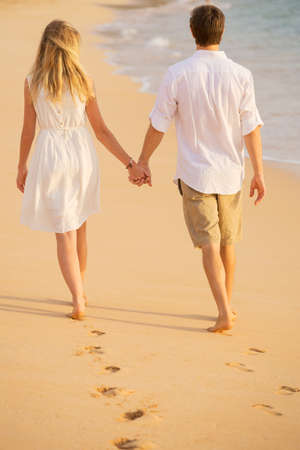 Romantic couple holding hands walking on beach at sunset. Man and woman in love. Footprints in the sand.  Stock Photo