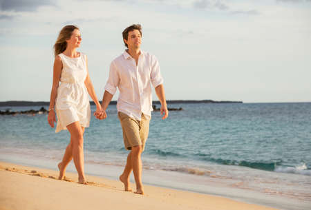 Romantic happy couple walking on beach at sunset. Smiling with arms around each other. Man and woman in love photo