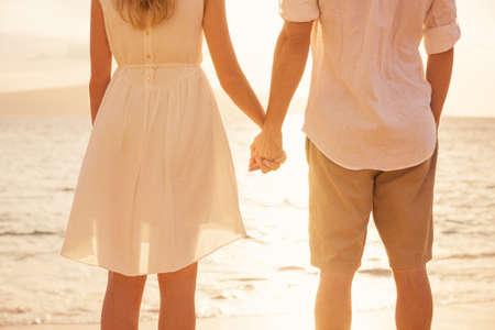 h�ndchen halten: Paar H�ndchen haltend bei Sonnenuntergang am Strand. Romantische junge Paar in der Liebe
