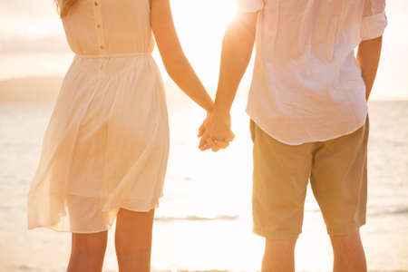 couple holding hands: Couple holding hands at sunset on beach. Romantic young couple in love