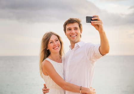 Happy romantic couple on the beach taking photo of themselves with smart phone at sunset, Man and woman in love  photo