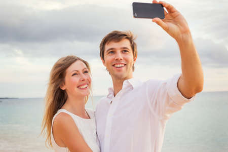 getaways: Feliz pareja rom�ntica en la playa tomando fotos de s� mismos con el tel�fono inteligente al atardecer, el hombre y la mujer en el amor