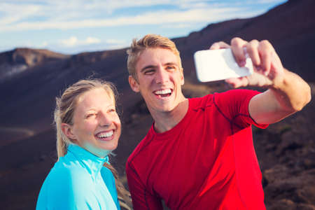 Young attractive athletic couple taking photo of themselves with smart phone, making a selfie photo