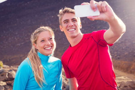 Young attractive athletic couple taking photo of themselves with smart phone, making a selfie