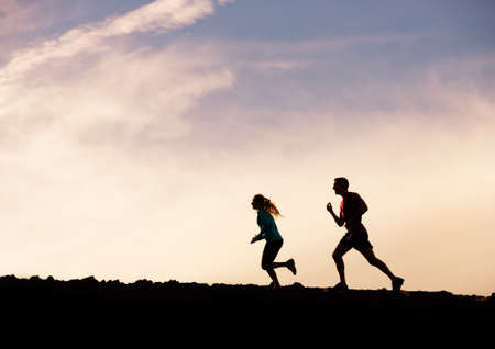 Silhouette of man and woman running jogging together into sunset, Wellness fitness concept photo