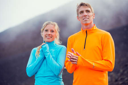 Young attractive athletic couple, wearing sporty cloths on trail outside in nature, relaxing after workout photo