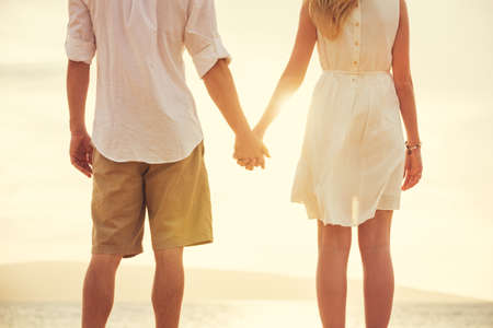 parejas caminando: Joven pareja de enamorados, hombre atractivo y la mujer disfruta de la tarde romántica en la playa, tomados de la mano viendo la puesta de sol