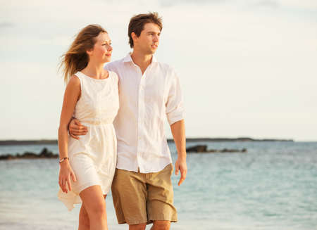 Young couple in love, Attractive man and woman enjoying romantic evening walk on the beach,  Watching the sunset photo