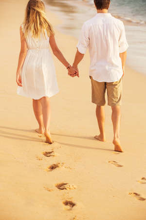 Young couple in love, Attractive man and woman enjoying romantic walk on the beach at sunset holding hands photo