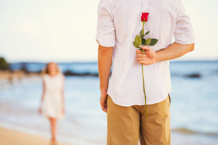 Young Couple in Love, Man holding surprise rose for beautiful young woman, Romantic Date