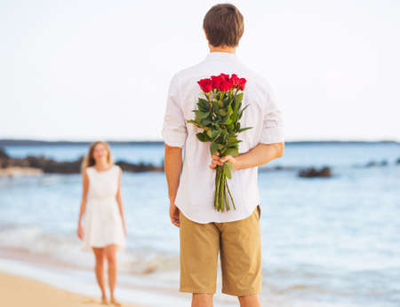 Young Couple in Love, Man holding surprise bouquet of roses for beautiful young woman, Romantic Date photo