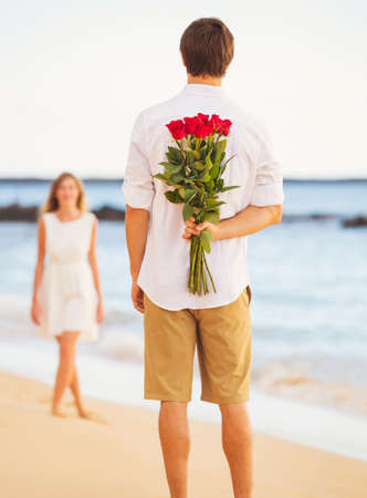 romance: Young Couple in Love, Man holding surprise bouquet of roses for beautiful young woman, Romantic Date