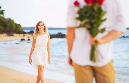 Young Couple in Love, Man holding surprise bouquet of roses for beautiful young woman, Romantic Date