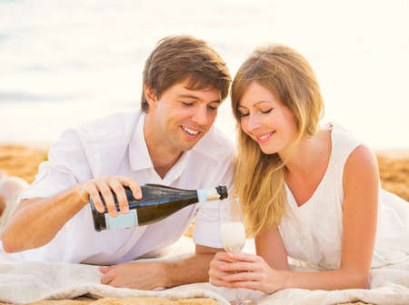 Honeymoon concept, Man and Woman in love, Couple enjoying glass of champagne on tropical beach at sunset photo