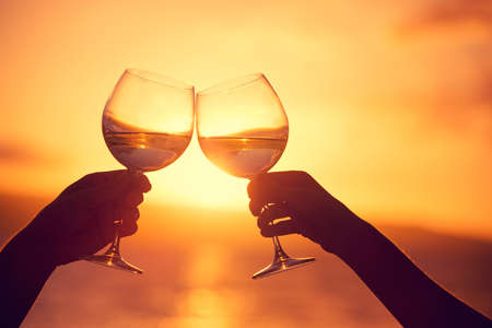 champers: Man and woman clanging wine glasses with champagne at sunset dramatic sky background Stock Photo