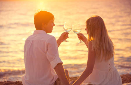 Honeymoon concept, Man and Woman in love, Couple enjoying glass of champagne on tropical beach at sunset, Beautiful sunset light photo
