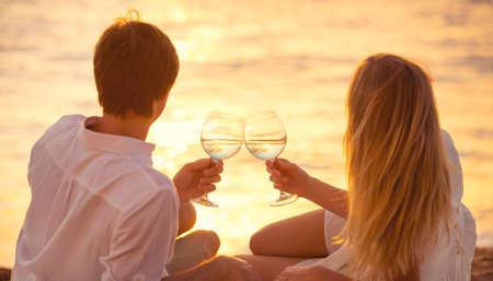 luna de miel: Concepto de luna de miel, el hombre y la mujer en el amor, pareja disfrutando de una copa de champán en la playa tropical al atardecer, luz del atardecer Hermosa Foto de archivo