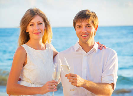 Man and Woman in love, Couple enjoying glass of champagne on tropical beach at sunset, Honeymoon concept photo