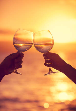 Man and woman clanging wine glasses with champagne at sunset dramatic sky background photo
