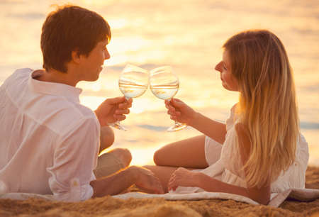 Honeymoon concept, Man and Woman in love, Couple enjoying glass of champagne on tropical beach at sunset, Beautiful sunset light Banco de Imagens