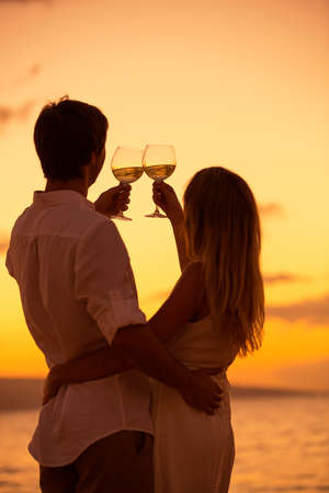 Silhouette of couple enjoying glass of champagne on tropical beach at sunset photo