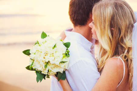 beach kiss: Bride holding bouquet of white flowers gazing at the ocean into the sunset