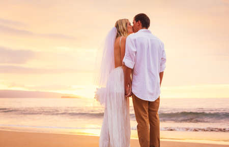 Bride and Groom, Enjoying Amazing Sunset on a Beautiful Tropical Beach, Romantic Married Couple Kissing photo