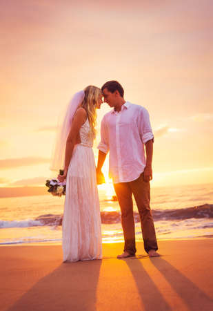 Bride and Groom, Enjoying Amazing Sunset on a Beautiful Tropical Beach, Romantic Married Couple Holding Hands, Just Married photo