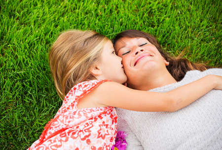 Happy mother and daughter relaxing outside on green grass. Spending quality time together, Real emotions photo