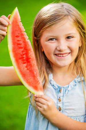 Cute little girl eating watermelon Фото со стока