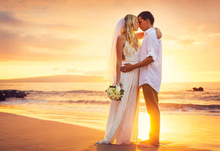 婚禮: 新娘和新郎,在日落的美麗的熱帶海灘接吻,浪漫的夫婦 版權商用圖片