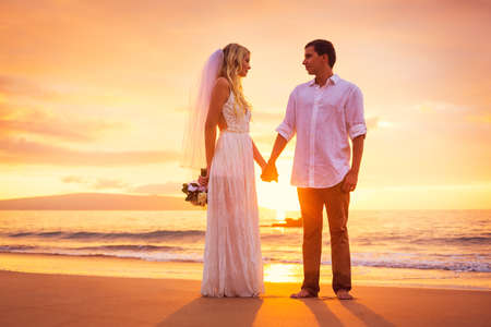 Bride and Groom, Enjoying Amazing Sunset on a Beautiful Tropical Beach, Romantic Married Couple Holding Hands photo