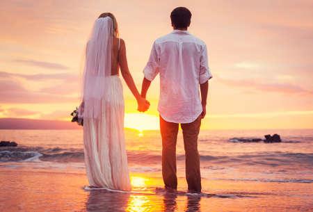 Bruid en bruidegom, genieten van geweldige zonsondergang op een prachtig tropisch strand, romantische echtpaar