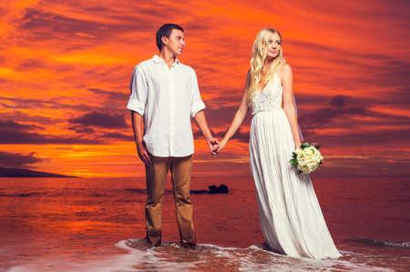 Sposa e sposo, godendo stupefacente Tramonto su una bella spiaggia tropicale, romantica coppia di sposi Holding Hands
