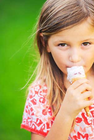 Happy cute little girl eating ice cream cone photo