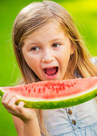 outsides: Cute little girl eating watermelon Stock Photo