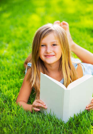 Cute little girl reading book outside on grass, relaxing outside in backyard photo