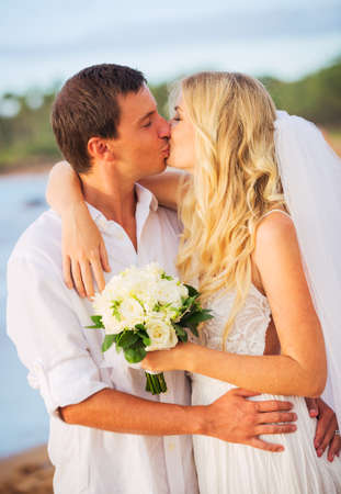 Bride and Groom, Kissing at Sunset on a Beautiful Tropical Beach, Romantic Married Couple photo