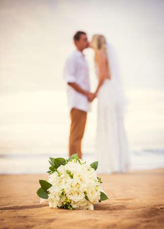 花嫁および新郎美しいトロピカル ・ ビーチで夕日を見て結婚されていたカップルのロマンチックな