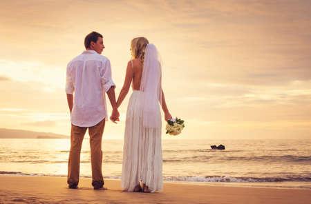 beach wedding: Bride and Groom, Enjoying Amazing Sunset on a Beautiful Tropical Beach, Romantic Married Couple Stock Photo